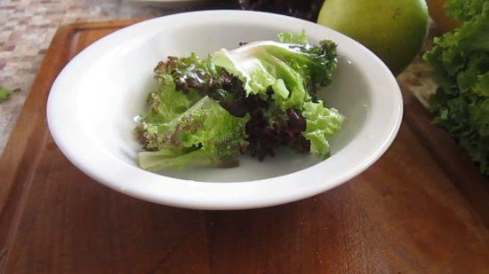 На дно тарелки выкладываем листья салата